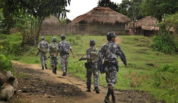Myanmar Border Guard Police (BGP) officers walk along a path ahead of journalists in Tin May village, in which Myanmar government and military claim the existence of Muslim terrorists, July 14, 2017