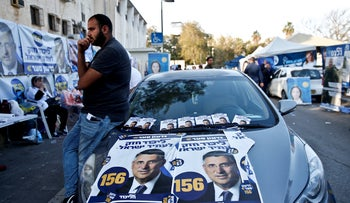 A man leans on a car with campaign posters for Gideon Sa'ar as Likud members vote on February 5, 2019.