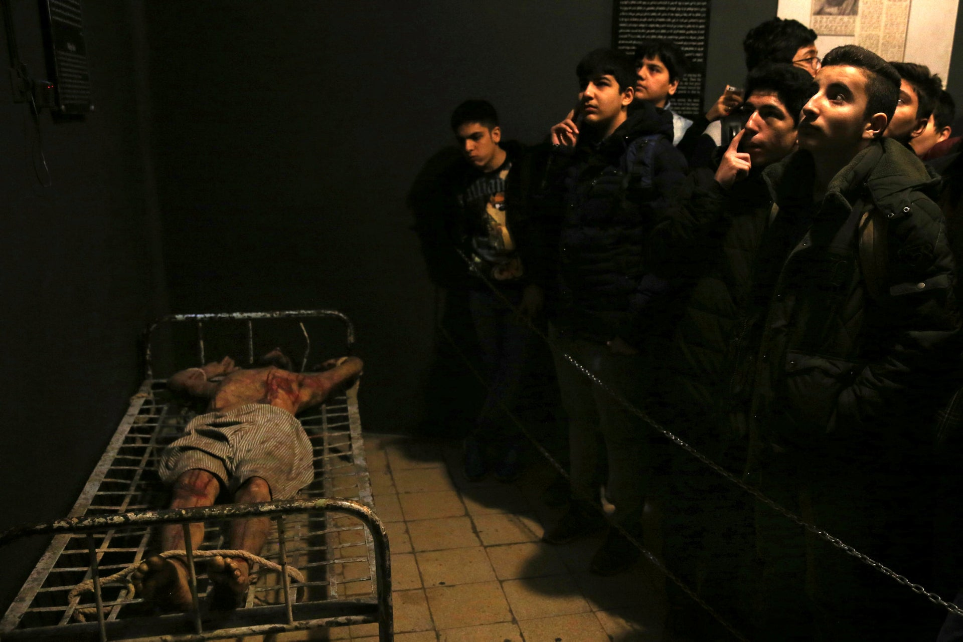 Iranian schoolboys look looks at an exhibition at a former prison, where a wax mannequin of a prisoner is tied to a bed, in Tehran, Iran, January 7, 2019.