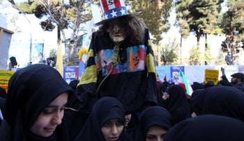 "A demonstrator holds an effigy of US government icon ""Uncle Sam"" during a rally in front of the former U.S. Embassy in Tehran, Iran, on Sunday, Nov. 4, 2018."