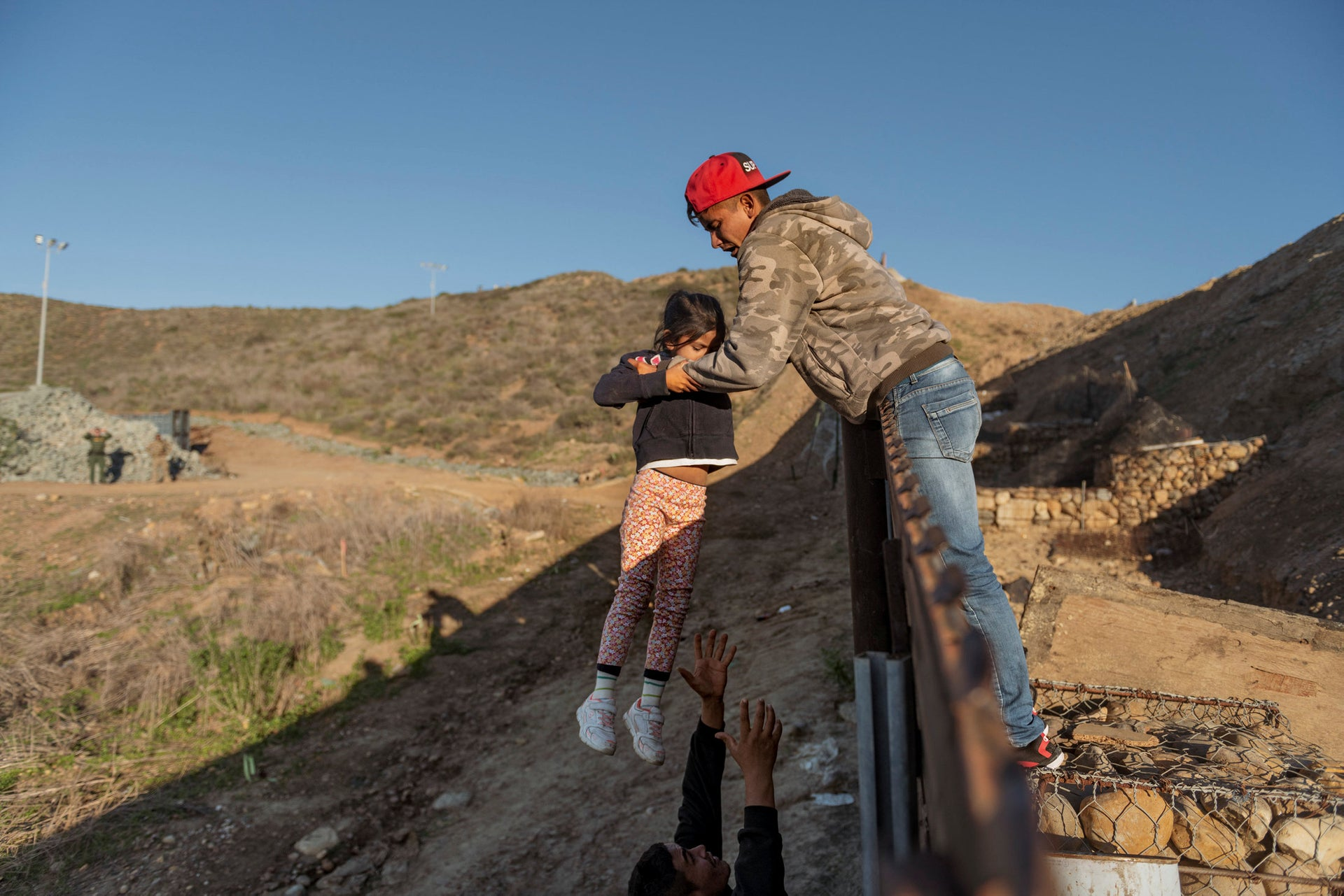 In this Jan. 3, 2019, file photo, a migrant from Honduras passes a child to her father after he jumped the border fence to get into the U.S. side to San Diego, Calif., from Tijuana, Mexico.