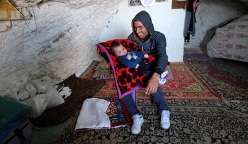 Yusuf Hanani and his son in their cave in Khirbet Tana. His first thought each morning is whether the Israel Defense Forces will come again that day to demolish his home.