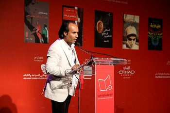 """Iraqi novelist, poet and screenwriter Ahmed Saadawi accepts the prize at the seventh International Prize for Arabic Fiction, for his book """"Frankenstein in Baghdad""""."""