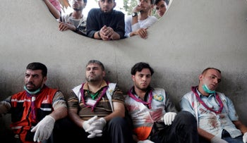 File photo: Palestinian medics rest after carrying wounded people injured from an Israeli strike in Shijaiyah neighborhood, into the emergency room at Gaza City's Shifa hospital, July 30, 2014.