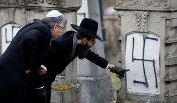 Grand Rabbi Harold-Abraham Weill inspects graves desecrated with swastikas in the Jewish cemetery of Herrlisheim, north of Strasbourg, France, December 14, 2018.