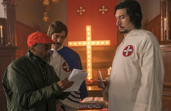 """This image released by Focus Features shows director Spike Lee, left, with actors Topher Grace, center, and Adam Driver on the set of Lee's film """"BlacKkKlansman."""""""
