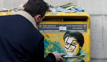 French street artist Christian Guemy, known as C215, cleans the vandalized mailboxes with swastikas covering the portrait of the late Holocaust survivor and renowned French politician Simone Veil, in Paris, February 12, 2019.