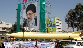 FILE Photo: A military exhibition displays a Revolutionary Guard missile, the  Shahab-3 missile, seen under a picture of the Iranian supreme leader Ayatollah Ali Khamenei, in Tehran, Iran.