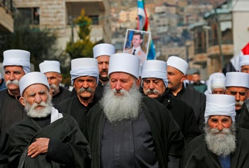 Druze residents of the Golan Heights carry a portrait of Syrian President Bashar Assad during a rally in the village of Majdal Shams, February 14, 2019.