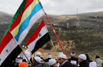Members of the Druze community hold Syrian and Druze flags as they sit facing Syria, during a rally marking the anniversary of Israel's annexation of the Golan Heights, February 14, 2019.