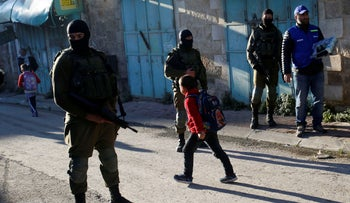 A Palestinian observer, right, watches as children walk past Israeli soldiers on their way to school in the West Bank city of Hebron, on February 12, 2019.
