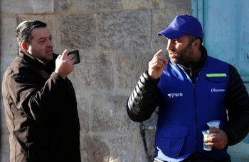 An Israeli settler takes a picture of a Palestinian observer as he watches over children walking to school in the West Bank city of Hebron, on February 12, 2019.