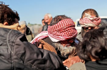 Alleged Islamic State fighters who fled from the frontline Syrian village of Baghouz sit blindfolded in the back of a pickup truck after being taken into custody by SDF forces, on January 30, 2019.