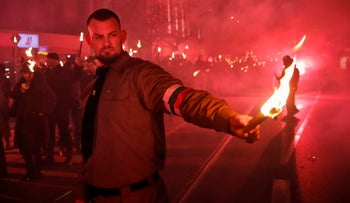 A man holds a flare as people take part in the 'Lukov March,' staged by the far-right Bulgarian National Union, in Sofia, Bulgaria, Feb. 16, 2019.