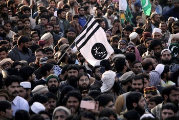 Supporters hold up the flag of Jaish-e-Mohammed, the militant organization led by Masood Azhar that took responsibility for the Kashmir attack, at a rally for Kashmir Day in Lahore, Pakistan. Feb. 5, 2019
