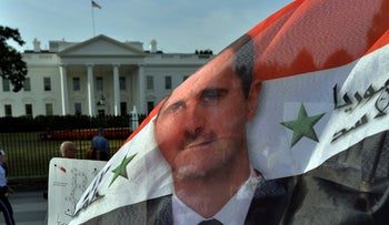 File Photo: Assad supporters wave a Syrian flag with Assad's flag on it during a demonstration in front of the White House in Washington, DC,September 9, 2013.
