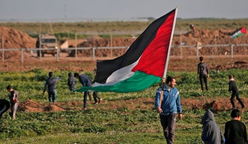 A Palestinian man carries the national flag during a demonstration near the fence along the border with Israel, east of Gaza City, February 8, 2019.