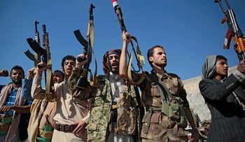 File Photo: Tribesmen loyal to Houthi rebels hold up their weapons as they attend a gathering to show their support for the ongoing peace talks being held in Sweden, in Sanaa, Yemen.