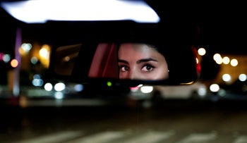 A Saudi woman drives her car down the capital's busy Tahlia Street after midnight for the first time, Riyadh, Saudi Arabia, June 24, 2018.