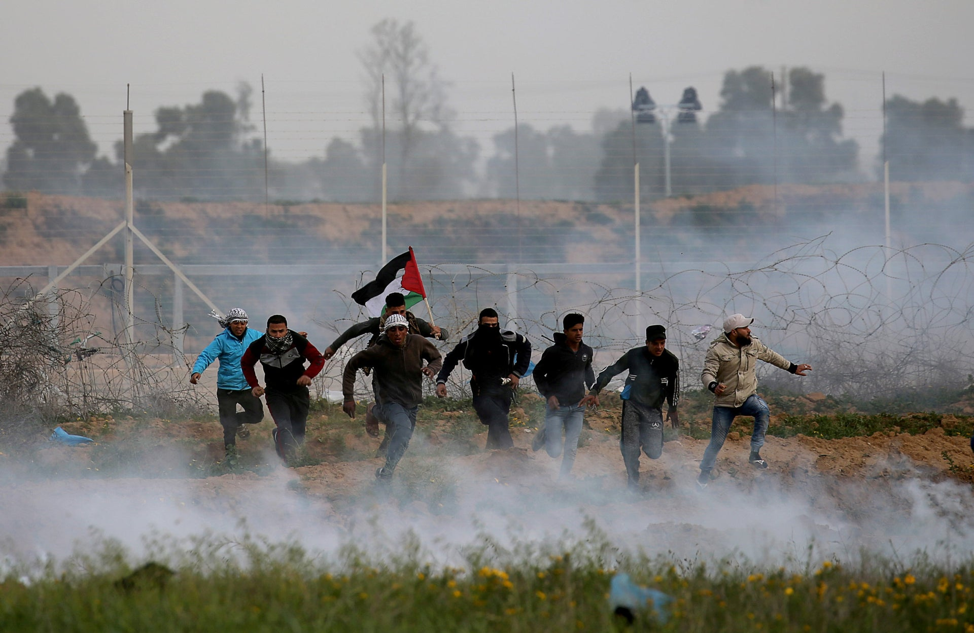 Palestinian demonstrators run away from Israeli fire and tear gas during a protest at the border fence in the southern Gaza Strip, February 15, 2019.