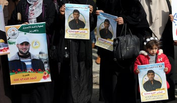 Families of Palestinian prisoners held in Israeli jails hold their pictures during a protest against wage cuts, in Gaza City, February 7, 2019.