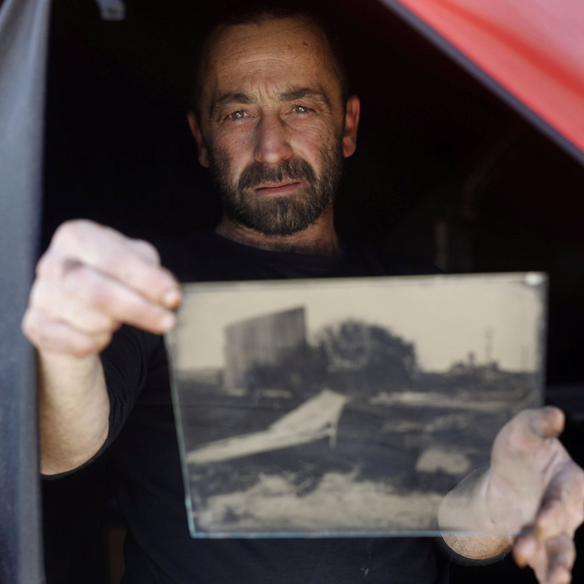 Photographer Edward Kaprov holds one of his images on a glass plate in his field darkroom, near Kibbutz Kissufim, on February 5 2019.
