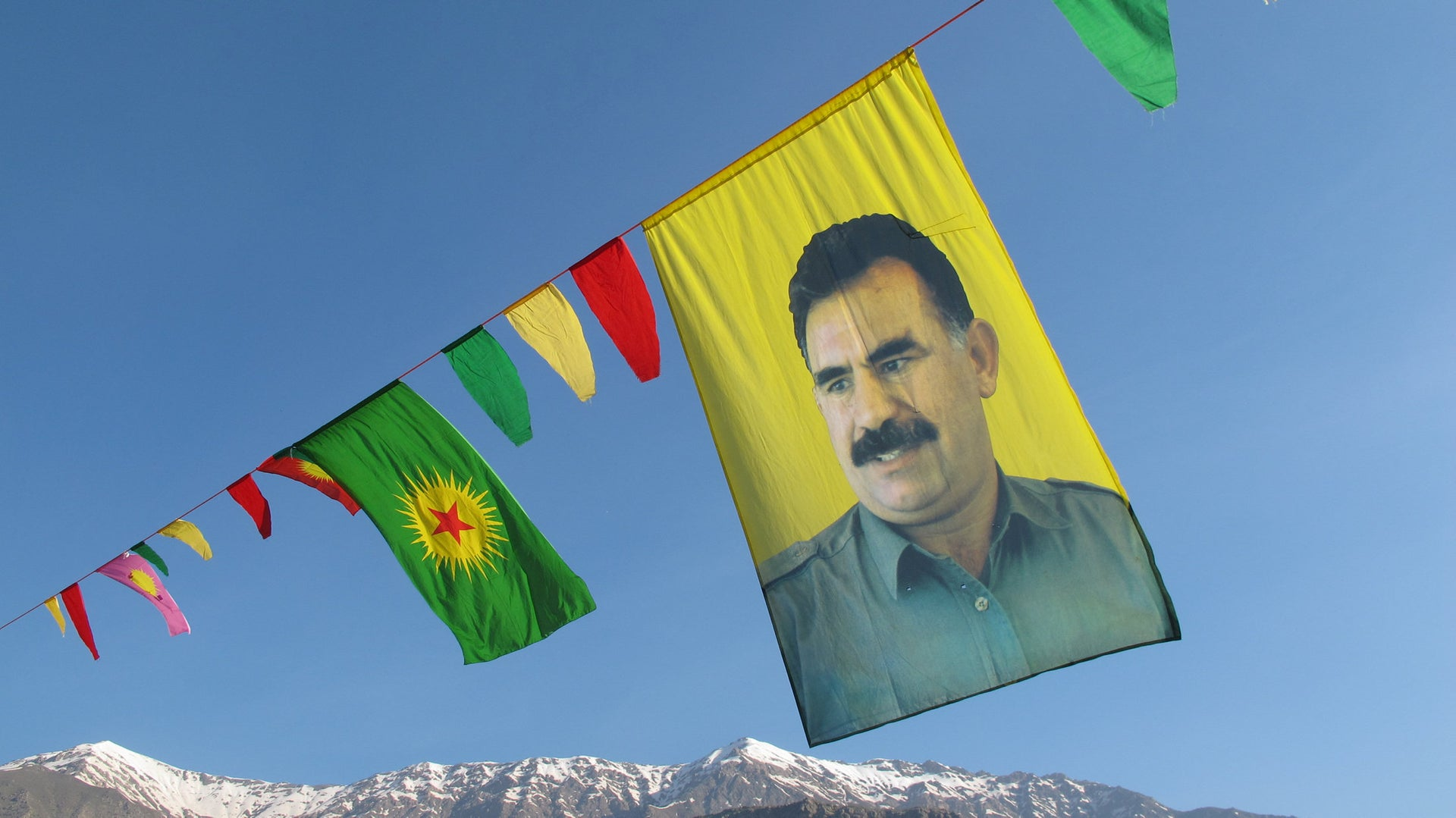 The Kurdish flag flies next to an image of Abdullah Öcalan, the leader of the PKK, who is serving a life sentence in a Turkish prison.