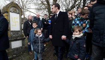 French President Emmanuel Macron walks past graves vandalized with swastikas at the Jewish cemetery in Quatzenheim, France, February 19, 2019.