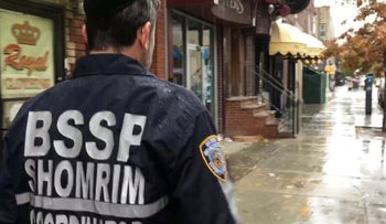 A Jewish neighborhood watch volunteer patrolling the streets of Brooklyn on a rainy day.