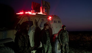 U.S.-backed Syrian Democratic Forces (SDF) stand next to an armored vehicle in the desert near the last land still held by Islamic State militants outside Baghouz, Syria, February 19, 2019.
