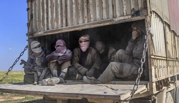 A truck carrying men identified as Islamic State group fighters who surrendered to Kurdish-led Syrian Democratic Forces drives through northern Syria, February 20, 2019.