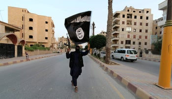 FILE Photo: A member loyal to the Islamic State waves an ISIS flag in Raqqa, Syria June 29, 2014.