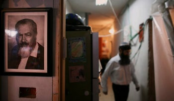 FILE PHOTO: With a portrait of late Jewish extremist leader Rabbi Meir Kahane on the wall, left, a Jewish settler walks inside a disputed building in the West Bank town of Hebron, November 16,  2008.