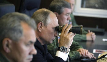 FILE PHOTO: Russian President Vladimir Putin uses a pair of binoculars while watching the Zapad-2017 war games at a military training ground in the Leningrad region, Russia September 18, 2017.