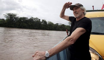 Musician and activist Roger Waters sails on a barge on Aguarico river after his visit to Aguarico 4 oil well at Amazon region in Ecuador, Monday, Nov. 19, 2018