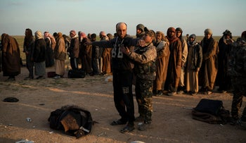 A man is frisked by a U.S.-backed Syrian Democratic Forces (SDF) fighter after being evacuated out of the last territory held by ISIS, near Baghouz, eastern Syria, February 22, 2019.