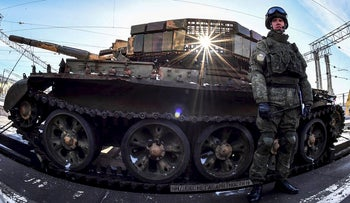 """Russian officer stands near the train with """"Syrian turning point"""" exhibition organised by Russian Defence Ministry stand on a open goods truck at Kazansky railway station in Moscow on February 23, 2019"""