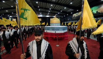 Party members carry Hezbollah flags as they stand in front of a replica of the Dome of the Rock during a rally marking Al-Quds day in Beirut's southern suburbs, Lebanon June 23, 2017.
