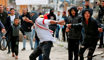 Palestinian protesters hurl stones at Israeli soldiers near Hebron's main street during an annual demonstration in memory of the 1994 Ibrahimi Mosque massacre, West Bank, February 22, 2019.
