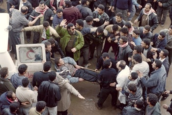 Palestinians evacuate an injured fellow after the Cave of the Patriarchs massacre carried out by Jewish settler Baruch Goldstein, Hebron, West Bank, February 25, 1994.