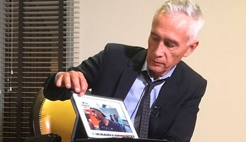 Univision's Jorge Ramos shows a video he says his crew shot the previous day showing Venezuelan youth picking food scraps out of the back of a garbage truck in Caracas, during an interview at a hotel in Caracas, Venezuela, Monday, Feb. 25, 2019