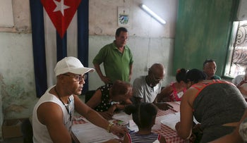 Election officials check the documents of a voter at a polling station during a constitutional referendum in Havana, Cuba, February 24, 2019