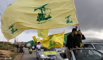FILE PHOTO: A supporter of Lebanon's Hezbollah gestures as he holds a Hezbollah flag in Marjayoun, Lebanon May 7, 2018.