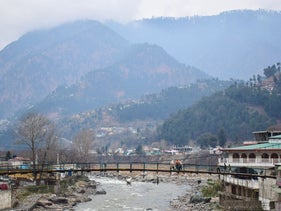 Pakistani residents walk on a bridge in the mountainous area of Balakot where the Indian Air Force (IAF) launched a raid, February 26, 2019.