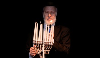 Chief Rabbi of Argentina, Gabriel Davidovich, holds a menorah at the AMIA Jewish community center..