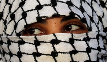 A girl covering her face with the Palestinian koofiyyeh scarf looks on during a protest at the Israel-Gaza border fence, in the southern Gaza Strip February 1, 2019