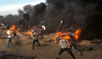 Palestinians hurl stones during a protest at the Gaza Strip's border with Israel October 5, 2018.