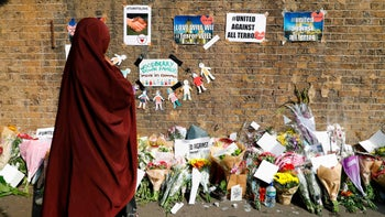 People stop to read tributes and look at plawers placed in the Finsbury Park area of north London on June 20, 2017, for the victims of a van attack on pedestrians nearby on June 19.