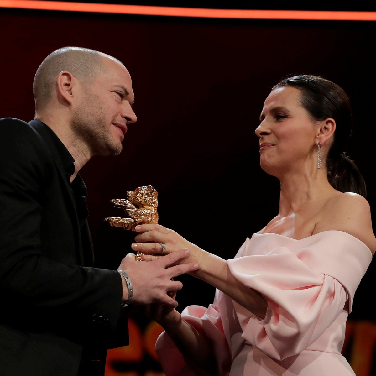 Director Nadav Lapid, left, receives the golden bear from jury president Juliette Binoche at the award ceremony of the 2019 Berlinale Film Festival in Berlin, Germany, Saturday, Feb. 16, 2019.