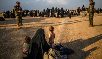 A woman and children wait along with others to be searched by members of the Syrian Democratic Forces after fleeing ISIS' last holdout of Baghouz, Syria, February 22, 2019.